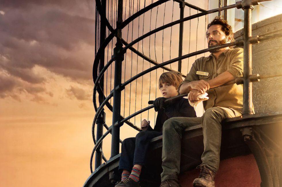 người đàn ông ngồi cạnh cậu bé trong phim điện ảnh The Lighthouse of the Orcas